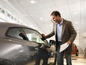 Male customer looks at car in dealership